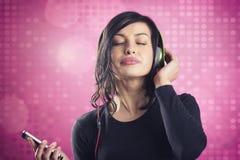 Szczęśliwa spokojna dziewczyna cieszy się słuchać muzyka z słuchawkami fotografia stock