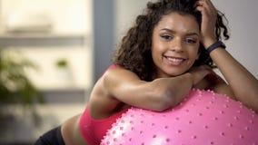 Szczęśliwa sport dziewczyna ono uśmiecha się przy kamerą, odpoczywa na sprawności fizycznej piłce po gym treningu fotografia stock