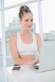 Szczęśliwa sportowa blondynka pisać na maszynie na laptopie Fotografia Royalty Free