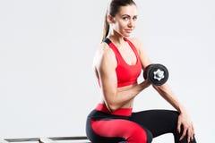 Szczęśliwa sportowa kobieta z dumbbells robi sporta ćwiczeniu, odosobnionemu na szarym tle obrazy stock