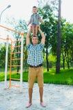 Szczęśliwa sporty chłopiec pozycja na mój father& x27; s ramiona Zdjęcia Royalty Free