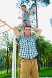 Szczęśliwa sporty chłopiec pozycja na mój father& x27; s ramiona Zdjęcie Stock