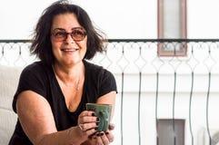 Szczęśliwa stara brunetki kobieta trzyma filiżankę kawy w ona ręki obrazy stock