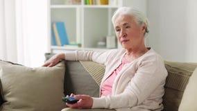 Szczęśliwa starsza kobieta ogląda tv w domu zbiory