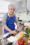 Szczęśliwa starsza kobieta w kuchennego narządzania świeżej ryba Zdjęcia Stock