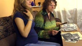 Szczęśliwa starsza kobieta z ciężarnymi wnuczka zegarka fotografiami Zdjęcia Royalty Free