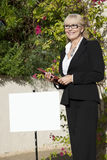 Szczęśliwa starsza kobiety pozycja znak deską z schowkiem Obrazy Royalty Free