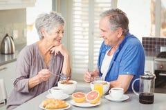 Szczęśliwa starsza para dyskutuje podczas gdy mieć śniadanie obraz royalty free
