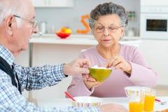 Szczęśliwa starsza para dyskutuje podczas gdy mieć śniadanie przy stołem zdjęcia stock