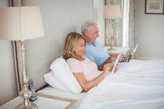 Szczęśliwa starsza para na łóżkowym używa laptopie i cyfrowej pastylce Zdjęcie Royalty Free