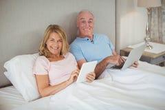 Szczęśliwa starsza para na łóżkowym używa laptopie i cyfrowej pastylce Zdjęcia Stock