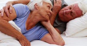 Szczęśliwa starsza para oddziała wzajemnie z each inny na łóżku zdjęcie wideo