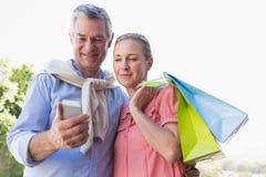Szczęśliwa starsza para patrzeje smartphone mienia torba na zakupy zdjęcie royalty free