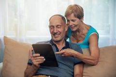 Szczęśliwa starsza para używa cyfrową pastylkę w domu zdjęcie royalty free
