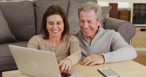 Szczęśliwa starsza para używa laptop na stolik do kawy fotografia stock