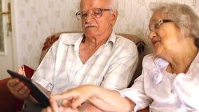 Szczęśliwa starsza para używa nowożytnego tablete zdjęcie wideo