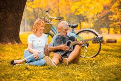 szczęśliwa starsza para w miłości bawić się gitarę akustyczną w parku pod dużym drzewem z rowerem w jesieni zdjęcie stock