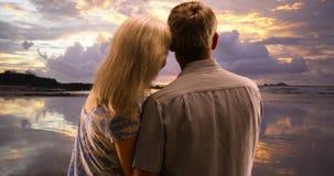Szczęśliwa starsza para w miłości ogląda zmierzch przy plażą obrazy royalty free