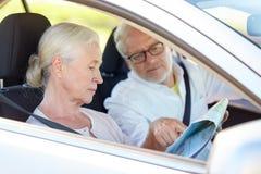 Szczęśliwa starsza para z mapy jeżdżeniem w samochodzie Zdjęcie Stock