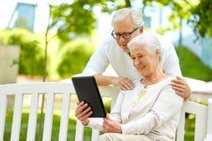 Szczęśliwa starsza para z pastylka komputerem osobistym przy lato parkiem Zdjęcia Royalty Free