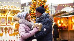 Szczęśliwa starsza para z prezentem przy bożymi narodzeniami wprowadzać na rynek zbiory