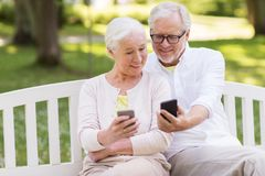 Szczęśliwa starsza para z smartphones przy parkiem Zdjęcie Royalty Free