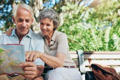 Szczęśliwa starsza turystyczna czytanie mapa zdjęcia royalty free