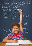Szczęśliwa studencka chłopiec przy stołową dźwiganie ręką przeciw błękitnemu blackboard z edukacją i szkół grafika zdjęcie royalty free