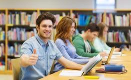 Szczęśliwa studencka chłopiec przygotowywa egzamin w bibliotece Fotografia Stock