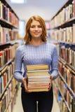 Szczęśliwa studencka dziewczyna lub kobieta z książkami w bibliotece Obraz Royalty Free