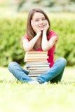 Szczęśliwa studencka dziewczyna target1369_1_ blisko stosu książki Obraz Stock