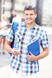 Szczęśliwa studencka pozycja w kampusie z jego smartphone fotografia royalty free