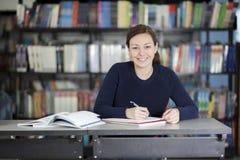 Szczęśliwa studencka robi praca domowa Obraz Royalty Free