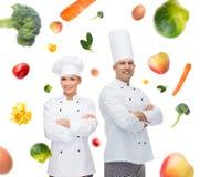 Szczęśliwa szef kuchni para, kucharzi nad karmowym tłem lub Obrazy Royalty Free