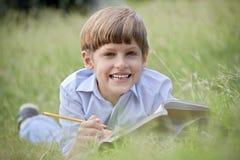 Szczęśliwa szkolna chłopiec robi pracie domowej i ono uśmiecha się, kłamający na trawie Zdjęcia Stock