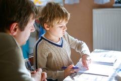 Szczęśliwa szkolna dzieciak chłopiec, ojciec robi pracie domowej i w domu zdjęcia royalty free