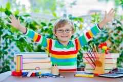 Szczęśliwa szkolna dzieciak chłopiec z szkłami i studenckim materiałem Obrazy Stock