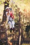 Szczęśliwa szkolna dziewczyna cieszy się aktywność w wspinaczkowym przygoda parku Obrazy Stock