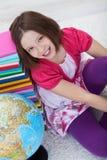 Szczęśliwa szkolna dziewczyna z książkami i kulą ziemską Zdjęcia Stock