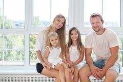 Szczęśliwa toung rodzina z dzieciakami w domu obrazy royalty free