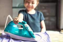 Szczęśliwa uśmiechnięta Śliczna mała dziewczynka odprasowywa koszula w domu Selecti zdjęcia royalty free