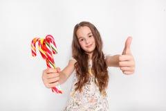 Szczęśliwa, uśmiechnięta śliczna mała dziewczynka z cristmas cukierku trzcinami, Mówić Ok Pozować przeciw białej ścianie Obraz Stock