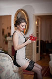 Szczęśliwa uśmiechnięta atrakcyjna kobieta jest ubranym elegancką suknię siedzi na kanapy ręki mieniu czarne pończochy i mała cze Zdjęcia Royalty Free