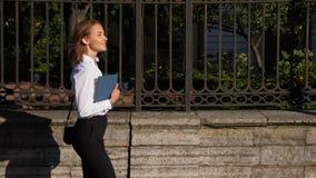 Szczęśliwa uśmiechnięta biznesowa kobieta chodzi samotnie z pastylki combuter zdjęcie wideo