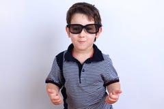 Szczęśliwa uśmiechnięta chłopiec w okularach przeciwsłonecznych pokazuje aprobaty gestykuluje, studi zdjęcia royalty free