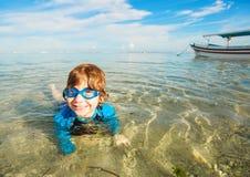 Szczęśliwa uśmiechnięta chłopiec z gogle na pływaniu w płyciznie Obrazy Royalty Free