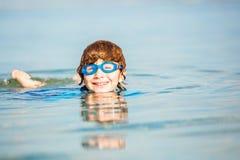 Szczęśliwa uśmiechnięta chłopiec z gogle na pływaniu w płyciznie Fotografia Stock