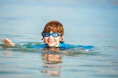Szczęśliwa uśmiechnięta chłopiec z gogle na pływaniu w płyciznie Obraz Royalty Free