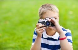 Szczęśliwa uśmiechnięta chłopiec z retro rocznik kamerą Fotografia Royalty Free