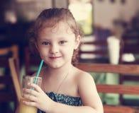 Szczęśliwa uśmiechnięta dzieciak dziewczyna pije świeżego sok od szkła w kawiarni Zdjęcie Stock
